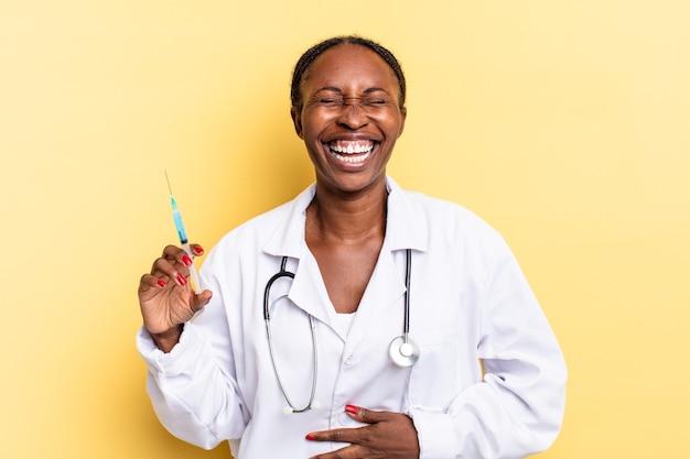 Śmiejąc się głośno z jakiegoś przezabawnego żartu, czując się szczęśliwym i wesołym, dobrze się bawiąc. koncepcja lekarza i strzykawki