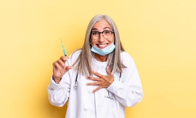 Śmiejąc się głośno z jakiegoś przezabawnego żartu, czując się szczęśliwym i wesołym, dobrze się bawiąc. koncepcja lekarza i szczepionki