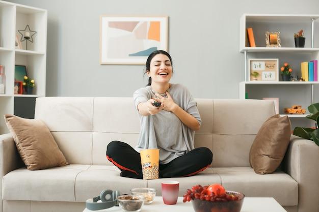 Śmiejąc się, kładąc dłoń na sercu młoda dziewczyna z wiadrem popcornu trzymająca pilota do telewizora, siedząca na kanapie za stolikiem kawowym w salonie