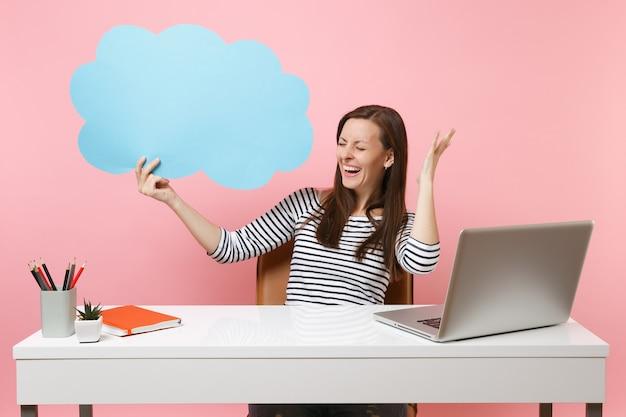 Śmiejąc się kobieta trzyma niebieski puste puste powiedz chmura dymek pracy na białym biurku z laptopem pc na białym tle na pastelowym różowym tle. koncepcja kariery biznesowej osiągnięcia. skopiuj miejsce na reklamę.