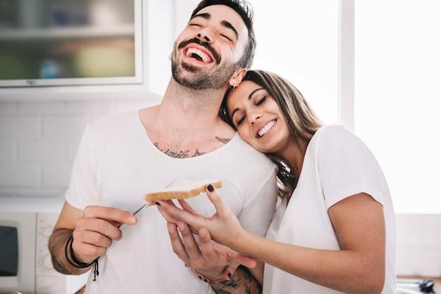 Śmiejąc się ludzie robią razem śniadanie