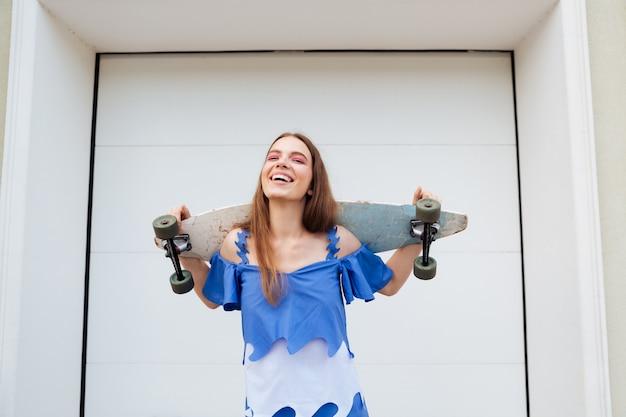 Śmiejąc się młoda dziewczyna stojąca z deskorolką na zewnątrz na tle białej ściany