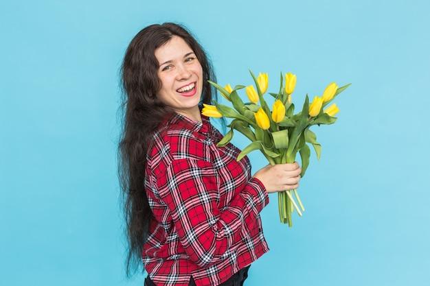 Śmiejąc się młoda kobieta kaukaski z bukietem tulipanów na niebieskiej ścianie