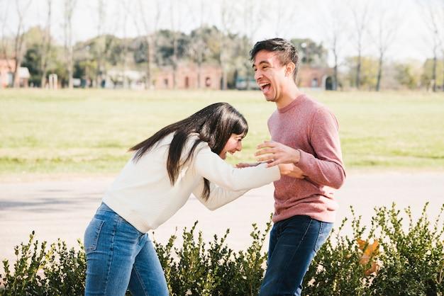 Śmiejąc się młoda kobieta łaskotanie człowieka