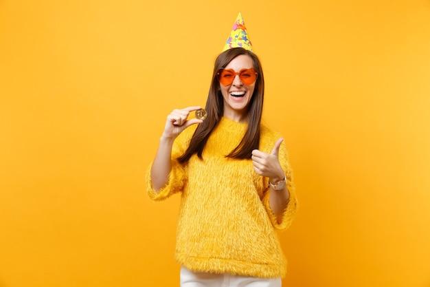 Śmiejąc się młoda kobieta w pomarańczowych okularach serca, urodziny kapelusz pokazując kciuk do góry, trzymając bitcoin metalową monetę złotego koloru przyszłej waluty na białym tle na żółtym tle. ludzie szczere emocje styl życia.