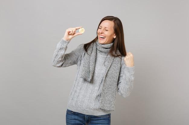 Śmiejąc się młoda kobieta w szarym swetrze, szalik zaciskając pięść jak zwycięzca trzymać bitcoin, przyszła waluta na białym tle na tle szarej ściany. zdrowy styl życia moda, emocje ludzi, koncepcja zimnej pory roku.