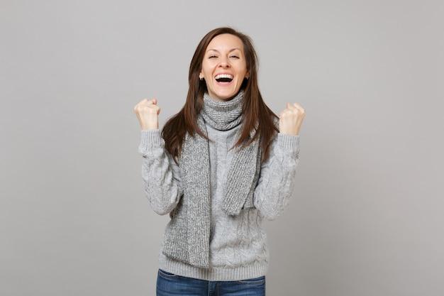 Śmiejąc się młoda kobieta w szarym swetrze, szalik zaciskając pięści jak zwycięzca na białym tle na tle szarej ściany. zdrowy styl życia moda, szczere emocje ludzi, koncepcja zimnej pory roku. makieta miejsca na kopię.