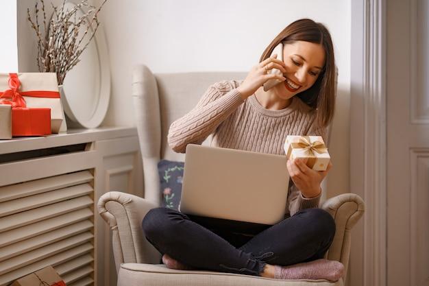 Śmiejąc się młoda kobieta z laptopa rozmawia przez telefon komórkowy, siedząc w wygodnym fotelu