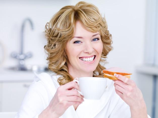 Śmiejąc się młoda piękna kobieta z filiżanką kawy jedząc śniadanie - w pomieszczeniu