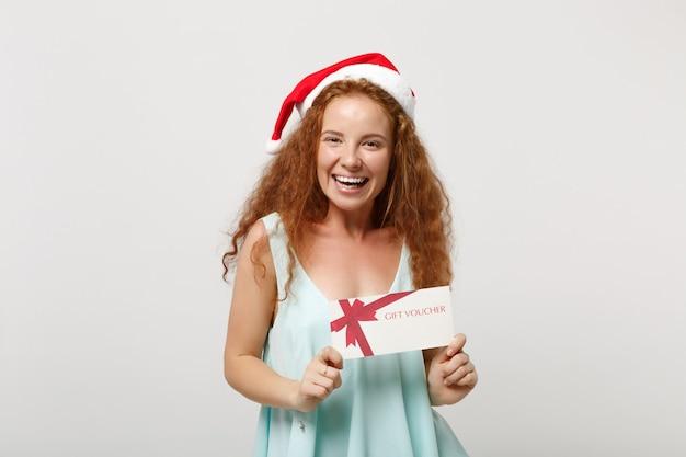 Śmiejąc się młoda rudowłosa dziewczyna santa w lekkie ubrania, świąteczny kapelusz na białym tle na białym tle w studio. szczęśliwego nowego roku 2020 celebracja wakacje koncepcja. makieta miejsca na kopię. posiadanie bonu upominkowego.