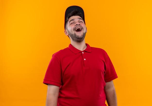Śmiejąc się młody człowiek dostawy w czerwonym mundurze i czapce