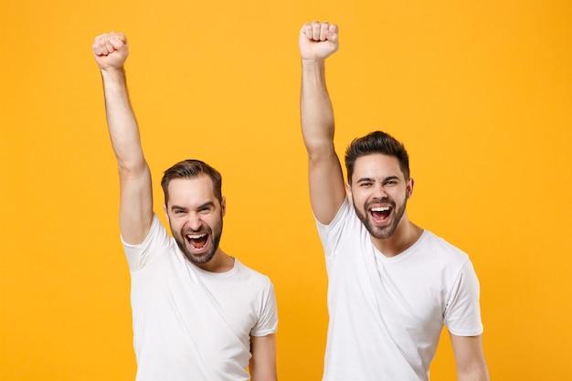 Śmiejąc się młodzi mężczyźni przyjaciele faceci w białych pustych pustych koszulkach pozowanie na białym tle na żółtej pomarańczowej ścianie w. koncepcja stylu życia ludzi. wznoszenie rąk robi gest zwycięzcy.