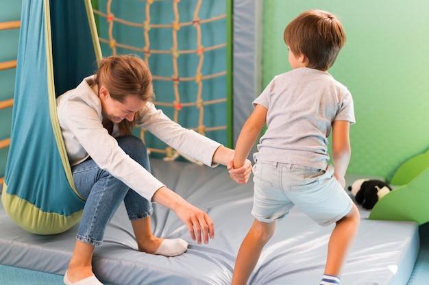 Śmiejąc się nauczyciel trzymający rękę dziecka