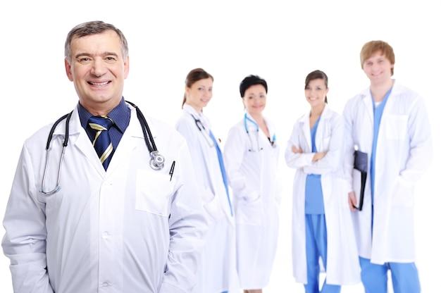 Śmiejąc się, odnoszący sukcesy, dojrzały lekarz płci męskiej z kolegami