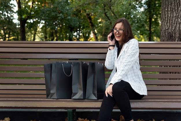 Śmiejąc się piękna kobieta rozmawia przez telefon. odpocznij w parku z torbami na zakupy. szczęśliwa młoda kobieta po zakupach.