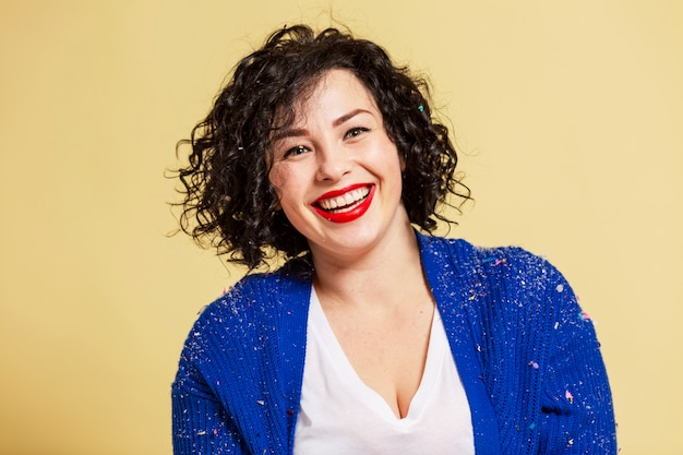 Śmiejąc się piękna młoda kobieta plus size w dżinsach i niebieskim swetrze. żółta ściana.
