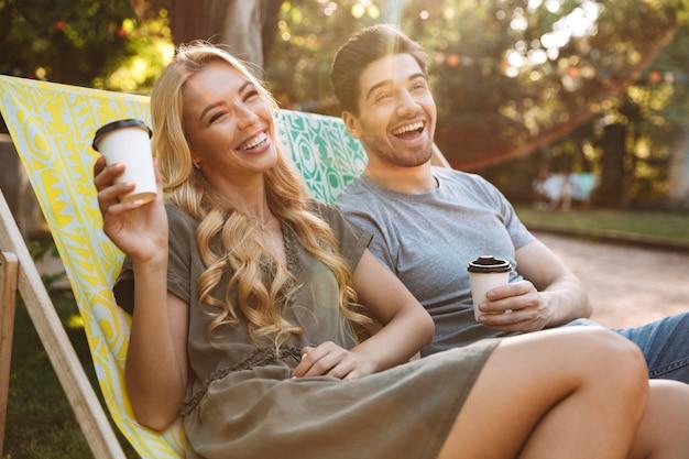 Śmiejąc się piękna młoda para siedzi razem na leżakach i patrząc na zewnątrz