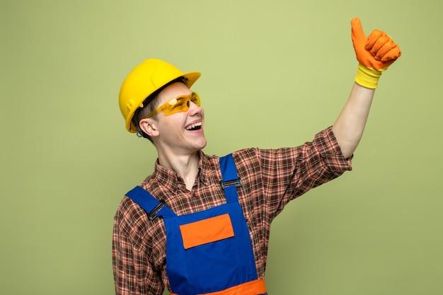 Śmiejąc się pokazując kciuk w górę młody mężczyzna budowniczy ubrany w mundur i rękawiczki w okularach