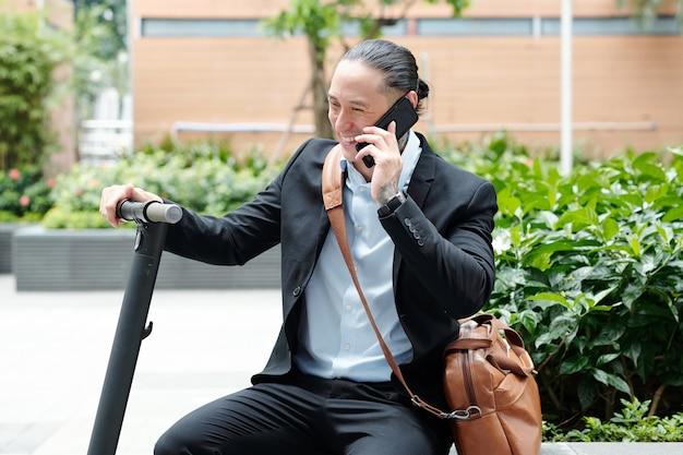 Śmiejąc się przystojny młody człowiek z hulajnogą siedzi na ławce i rozmawia przez telefon ze współpracownikiem lub przyjacielem
