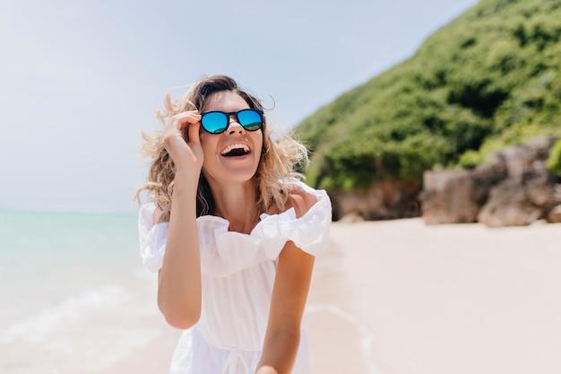Śmiejąc się spektakularna kobieta w okularach przeciwsłonecznych, ciesząc się wakacjami na tropikalnej wyspie. zewnątrz zdjęcie sympatycznej kobiety w białej sukni, uśmiechając się na przyrodę.