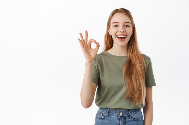 Śmiejąc się szczęśliwa szczera dziewczyna, pokazując znak ok ok i kiwając głową z aprobatą, zgadzam się, lubię i chwalić coś dobrego, komplementować, polecać doskonały produkt, stojąc nad białą ścianą