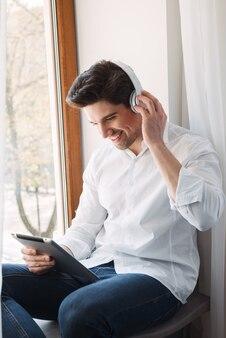Śmiejąc się szczęśliwy człowiek ubrany w białą koszulę za pomocą komputera typu tablet i słuchawek, siedząc przy oknie w salonie