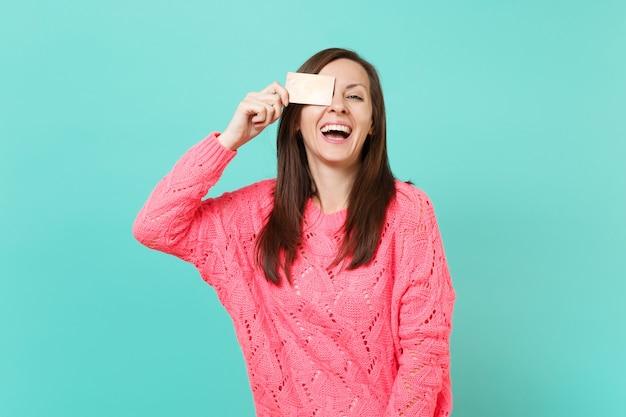 Śmiejąc się wesoła młoda kobieta w różowy sweter z dzianiny obejmujące oko z karty kredytowej w ręku na białym tle na tle niebieskiej ściany turkus, portret. koncepcja życia ludzi. makieta miejsca na kopię.