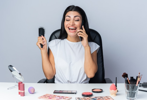 Śmiejąc się z zamkniętymi oczami, piękna kobieta siedzi przy stole z narzędziami do makijażu, trzymając grzebień, mówi przez telefon