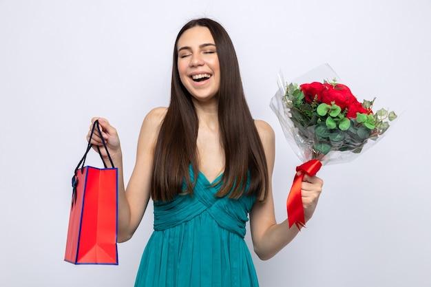 Śmiejąc się z zamkniętymi oczami piękna młoda dziewczyna na szczęśliwych walentynek trzyma bukiet z torbą na prezent