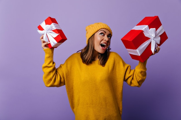 Śmiejąc się zadowolony dziewczyna w żółtym stroju, ciesząc się ferie zimowe. portret spektakularnej kobiety przygotowującej prezenty na nowy rok.