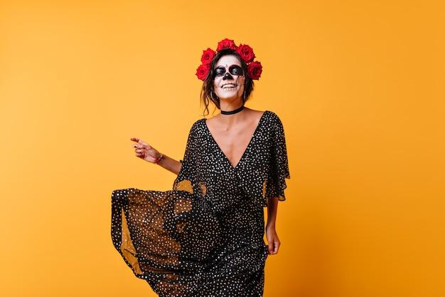 Śmiejąc się żeński zombie z różami we włosach, taniec w studio. szczęśliwa dziewczyna z meksykańskim makijażem świętuje halloween.