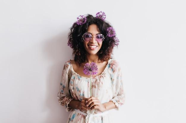 Śmiejąca się afrykańska dziewczyna z czarnymi włosami z fioletowymi kwiatami. czarująca kręcona dama w okularach przeciwsłonecznych trzymająca alium.