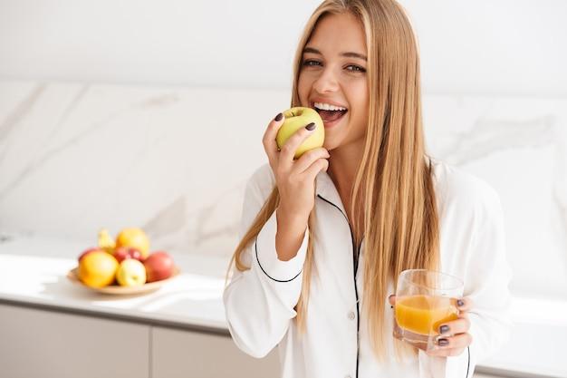 Śmiejąca się atrakcyjna kobieta w piżamie jedząca jabłko i pijąca sok stojąc w jasnej kuchni