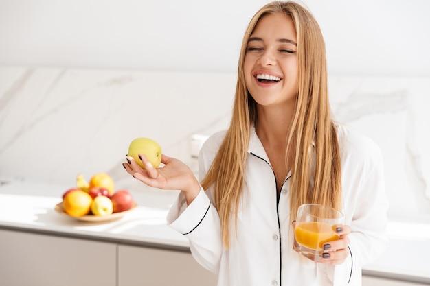Śmiejąca się atrakcyjna kobieta w piżamie trzymająca jabłko i pijąca sok, stojąc w jasnej kuchni
