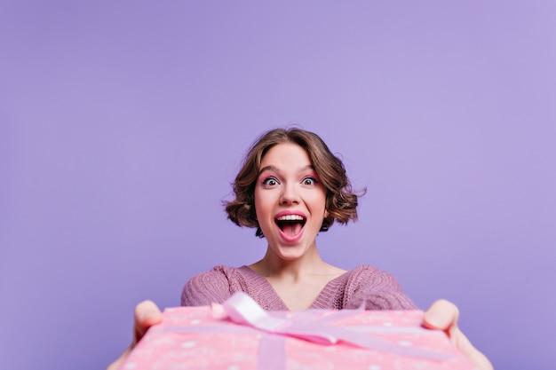 Śmiejąca się brunet dziewczyna na białym tle na fioletowej ścianie z dużym prezentem urodzinowym. kryty zdjęcie ślicznej krótkowłosej dziewczyny trzymającej świąteczne pudełko ozdobione wstążką.
