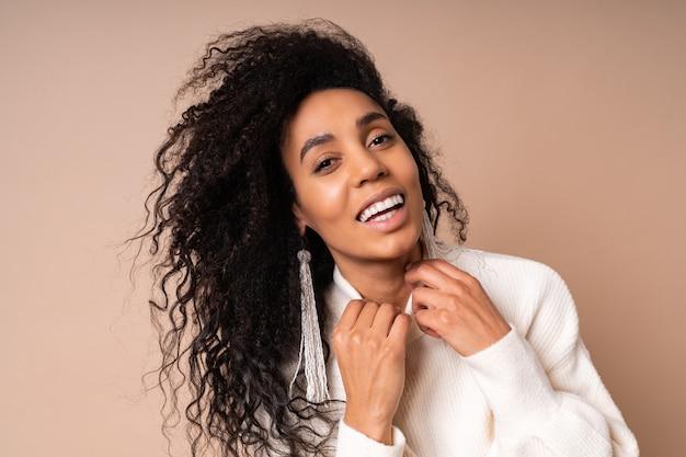 Śmiejąca się brunetka kręcona brązowa kobieta w białym swetrze na co dzień pozuje na beżu
