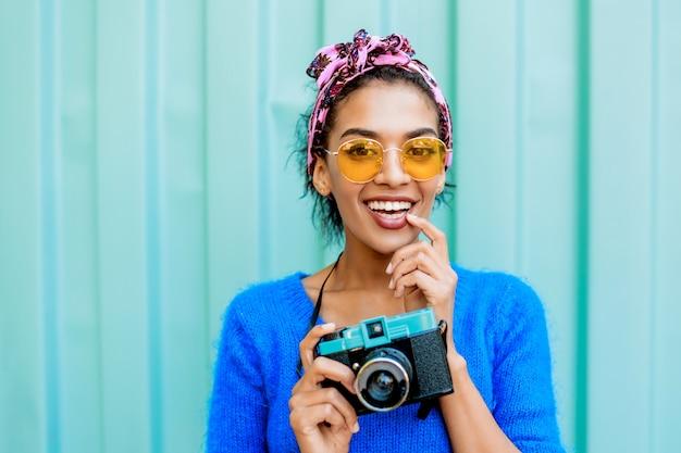 Śmiejąca się czarna dziewczyna z ładny fryzury, trzymając aparat retro i patrząc na kamery.