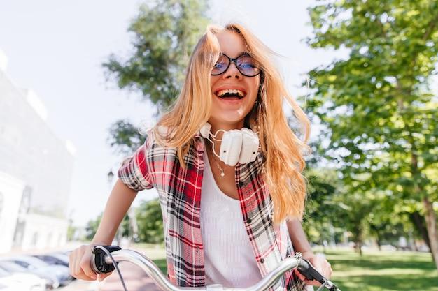 Śmiejąca się czarująca dziewczyna pozuje w parku. podekscytowana pani w zwykłym ubraniu wyrażająca szczęście w letni dzień.