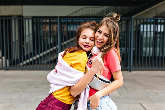 Śmiejąca się długowłosa dziewczyna w różowej koszuli stojącej z ręką w kieszeni, podczas gdy jej siostra brunetka przytula ją z zamkniętymi oczami