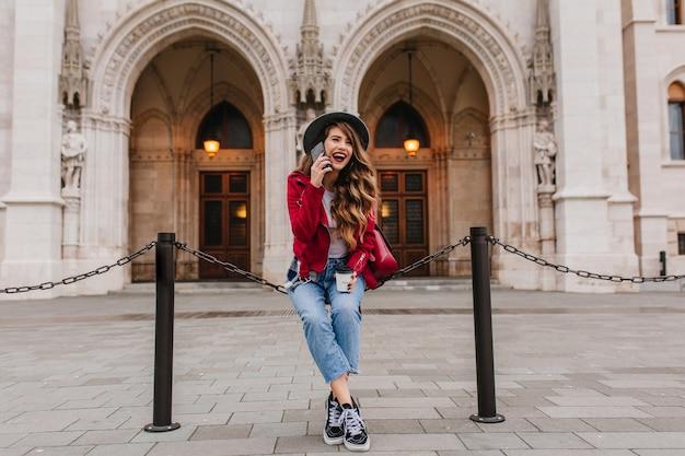 Śmiejąca się długowłosa kobieta w dżinsach i czerwonej kurtce, siedząc przed starym pięknym muzeum