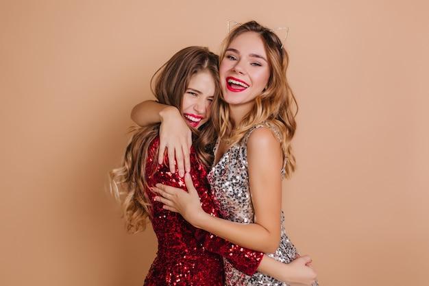 Śmiejąca się długowłosa kobieta z jasnym makijażem obejmująca kręconą siostrę na beżowej ścianie