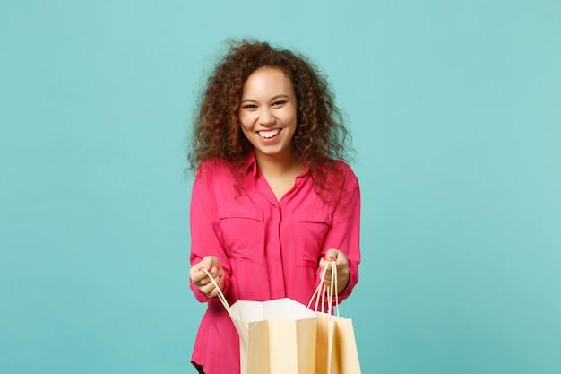 Śmiejąca się dziewczyna afryki w różowe ubrania dorywczo trzymać pakiet torba z zakupami po zakupach na białym tle na tle niebieskiej ściany turkus. koncepcja życia szczere emocje ludzi. makieta miejsca na kopię.