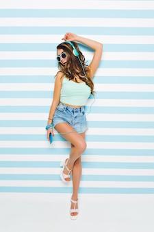 Śmiejąca się dziewczyna w eleganckich sandałach na obcasie i stylowych okularach przeciwsłonecznych stojących na jednej nodze pozuje na pasiastej ścianie. portret młodej damy słuchania piosenki w słuchawkach i śpiewu, trzymając telefon.
