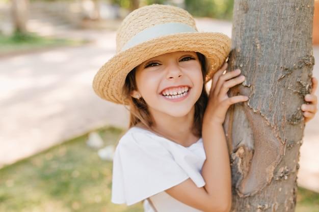 Śmiejąca się dziewczynka z lekko opaloną skórą pozuje w parku dotykając drzewa. zewnątrz portret szczegół wesoły ciemnowłosy dzieciak w kapeluszu vintage z wstążką, zabawy w ogrodzie.