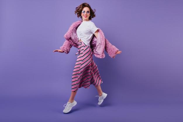 Śmiejąca się fascynująca dziewczyna w białych trampkach skacząca na fioletowej ścianie. pełnometrażowe zdjęcie rozentuzjazmowanej młodej kobiety z falującymi włosami tańczącymi.