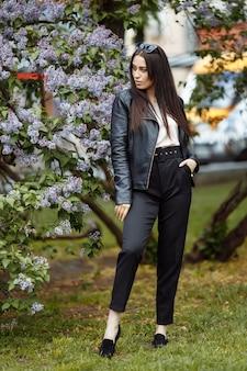Śmiejąca się i uśmiechnięta piękna szczęśliwa artystyczna młoda modelka z długimi włosami w letnim liliowym ogrodzie z kwiatami pozującymi do kamery bawi się koncepcją włosów