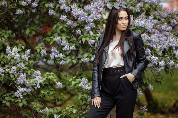 Śmiejąca się i uśmiechnięta piękna szczęśliwa artystyczna młoda modelka z długimi włosami w letnim ogrodzie bzu z kwiatami pozuje do aparatu