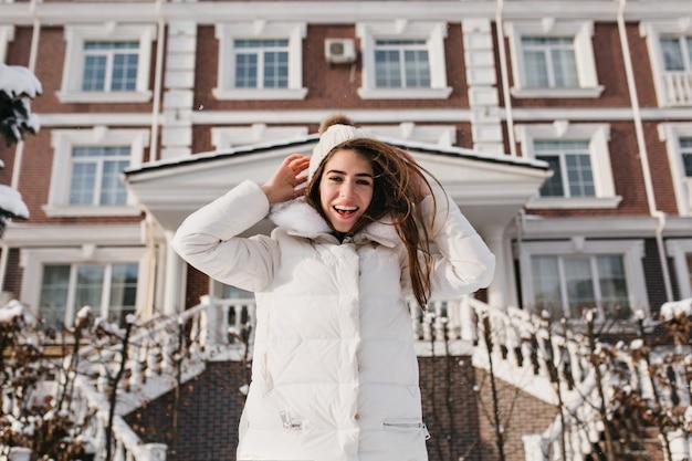Śmiejąca się kobieta o ciemnych włosach, ciesząc się ciepłym zimowym dniem i robiąc śmieszne miny. plenerowe zdjęcie beztroskiej modelki w białym stroju, schładzającej się w pobliżu domu w grudniu.