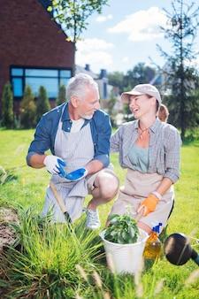 Śmiejąca się kobieta. piękna kobieta, śmiejąc się, słuchając swojego zabawnego przystojnego męża podczas pracy w ogrodzie