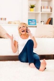 Śmiejąca się kobieta rozmawia przez telefon w salonie